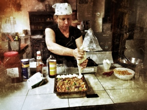 Stacy adding mashed potato layer to her vegan Shepherd's Pie