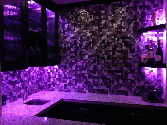 Finished wet bar with ceiling raised, new cabinets,  countertops, tile and accent lighting.